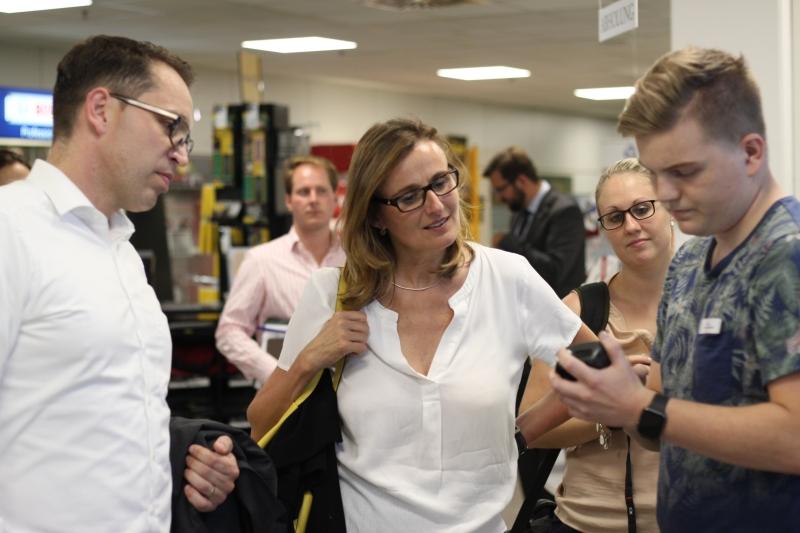 Staatssekretärin Katrin Schütz und Boris Behringer begutachten interessiert die elektronische Kommissionierung durch einen Auszubildenden von ZANDER.